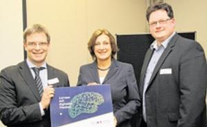 Das Schild für die Schule: Bildungsministerin Britta Ernst überreicht es an Sven-Eric Leisner (links) und Gerrit Lange. Foto: vaquette